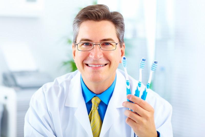dentysta polecający szczoteczki do zębów